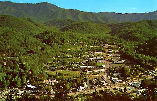 1965 03 21 GATLINBURG, TENNESSEE AS SEEN FROM THE UPPER TERNIMAL OF THE SKYLIFT ON CROCKETT MOUNTAIN. This view is made looking up Airport Road. Mt LeConte may be seen in the distance at the left..jpg